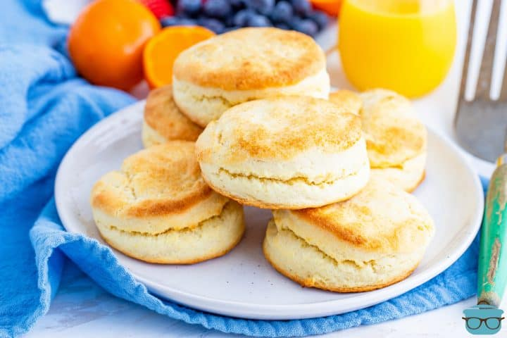 Cream Biscuits stacked on a round white plate with a glass of orange juice in the background