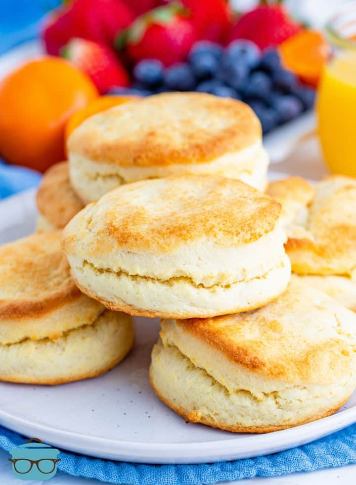 Cream Biscuits stacked on a white plate with fresh fruit in the background