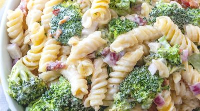 Creamy Bacon Broccoli Pasta Salad in a large white serving bowl surrounded by a white and yellow dish towel