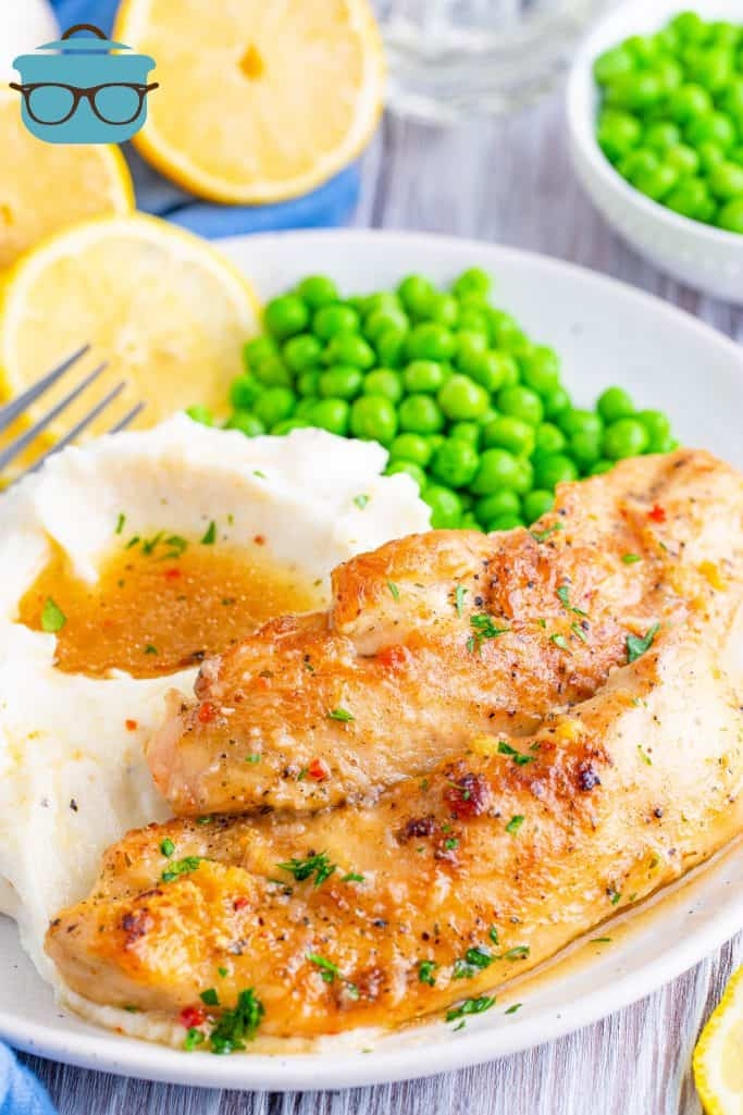 two slices of lemon garlic chicken tenders on a white plate with a side of mashed potatoes and peas