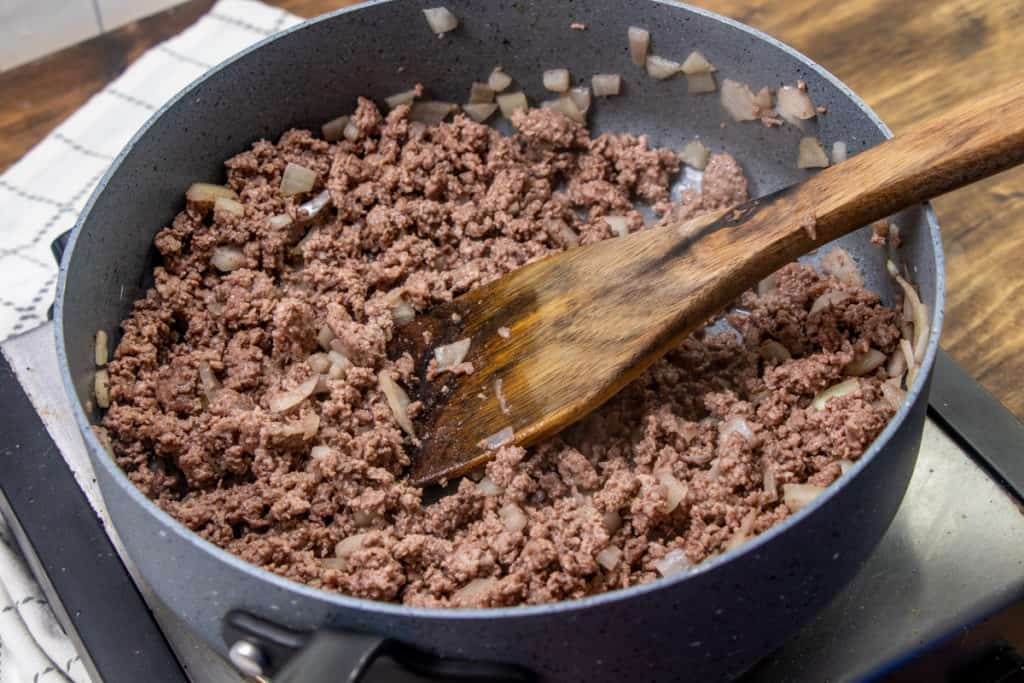 browning and crumbling ground beef with onion in a large saucepan