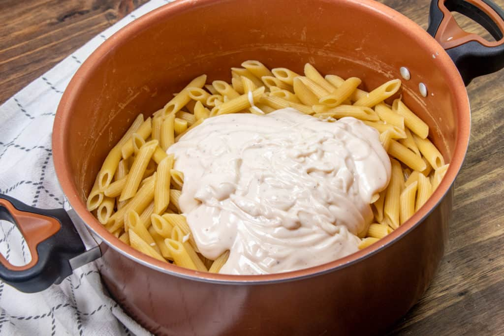 cooked penne pasta in a large stock pot - topped with Alfredo sauce