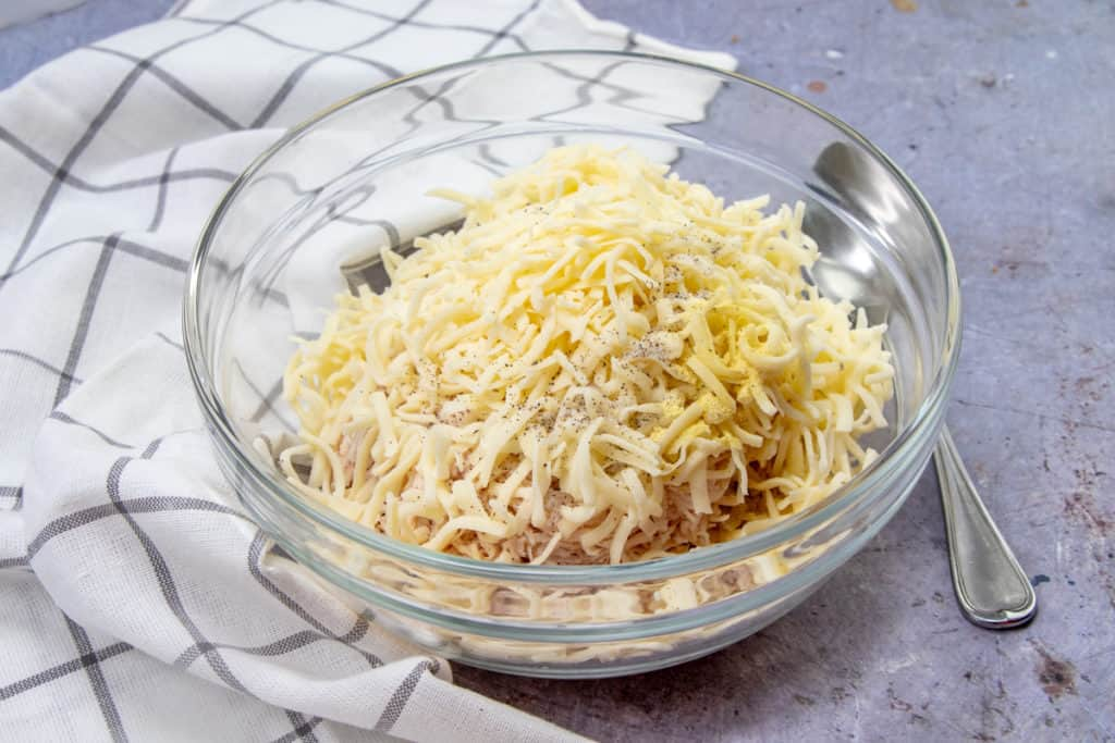 shredded chicken, shredded cheese, salt, pepper, Adobo seasoning in a medium glass bowl