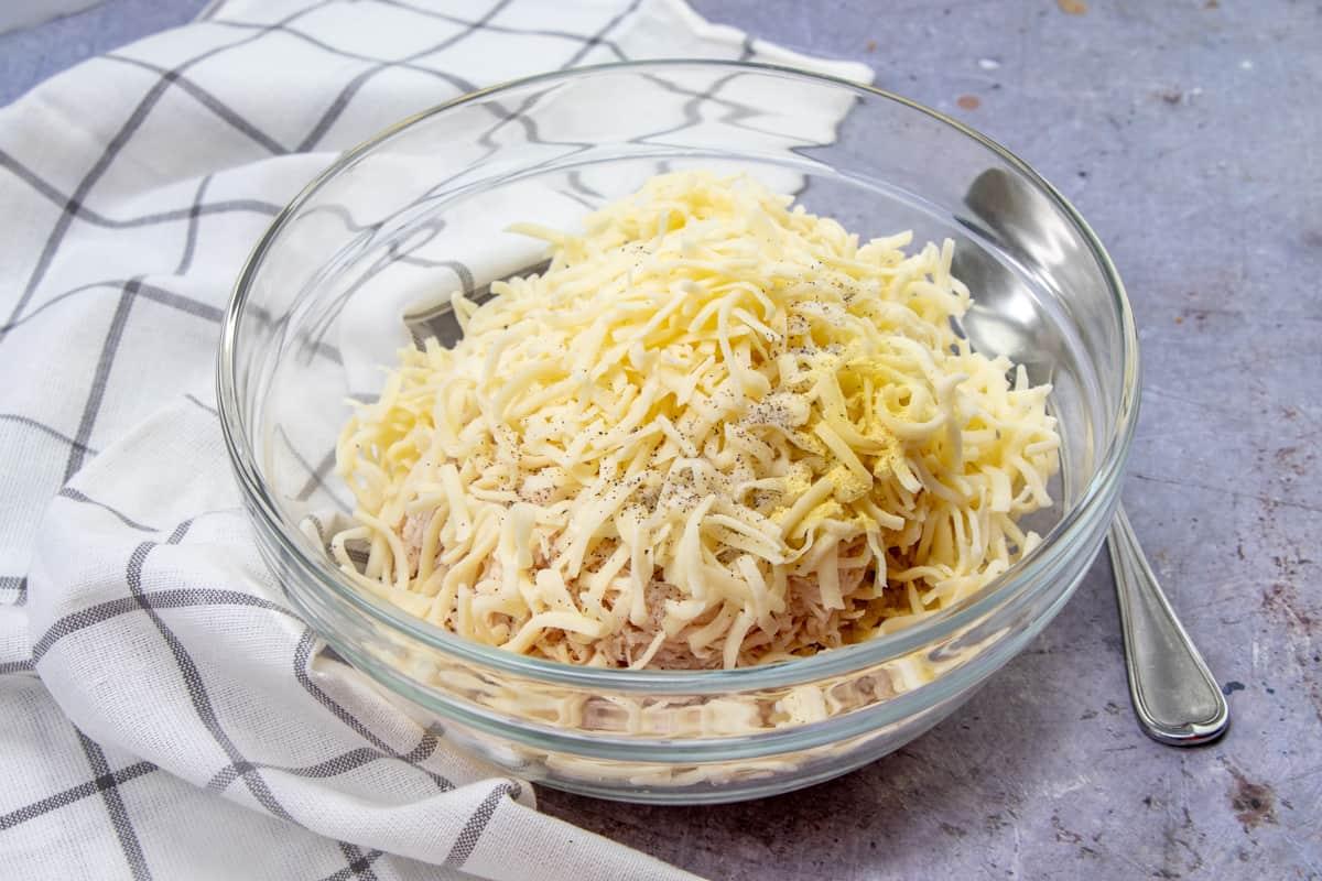 shredded chicken, shredded cheese, salt, pepper, Adobo seasoning in a medium glass bowl