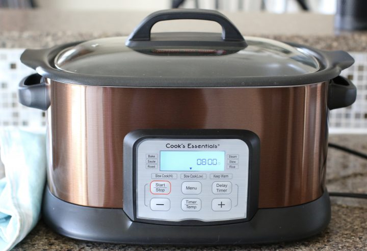 brown oval slow cooker showing a clock set to eight hours