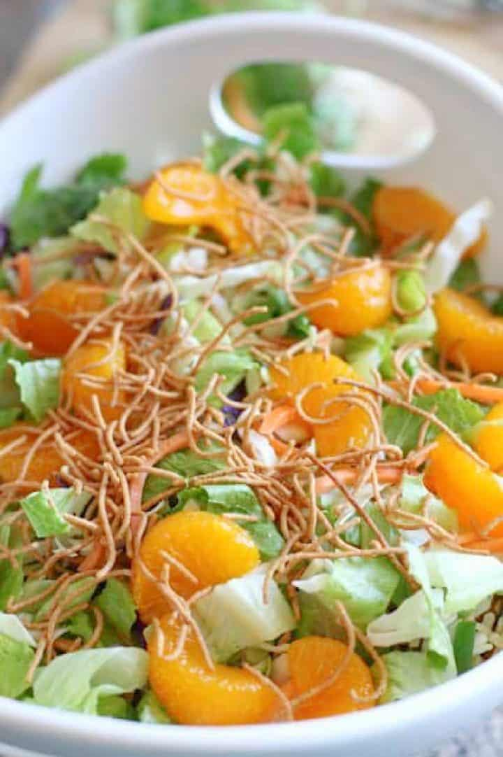 Mandarin oranges, chow mein noodles added to diced romaine lettuce, cole slaw and green onions in a white bowl with handles.