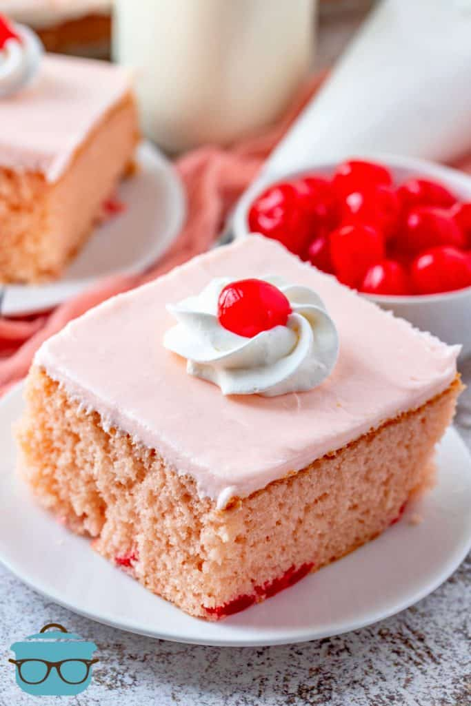 slice f maraschino cherry cake on a small white plate with a bowl of maraschino cherries in the background