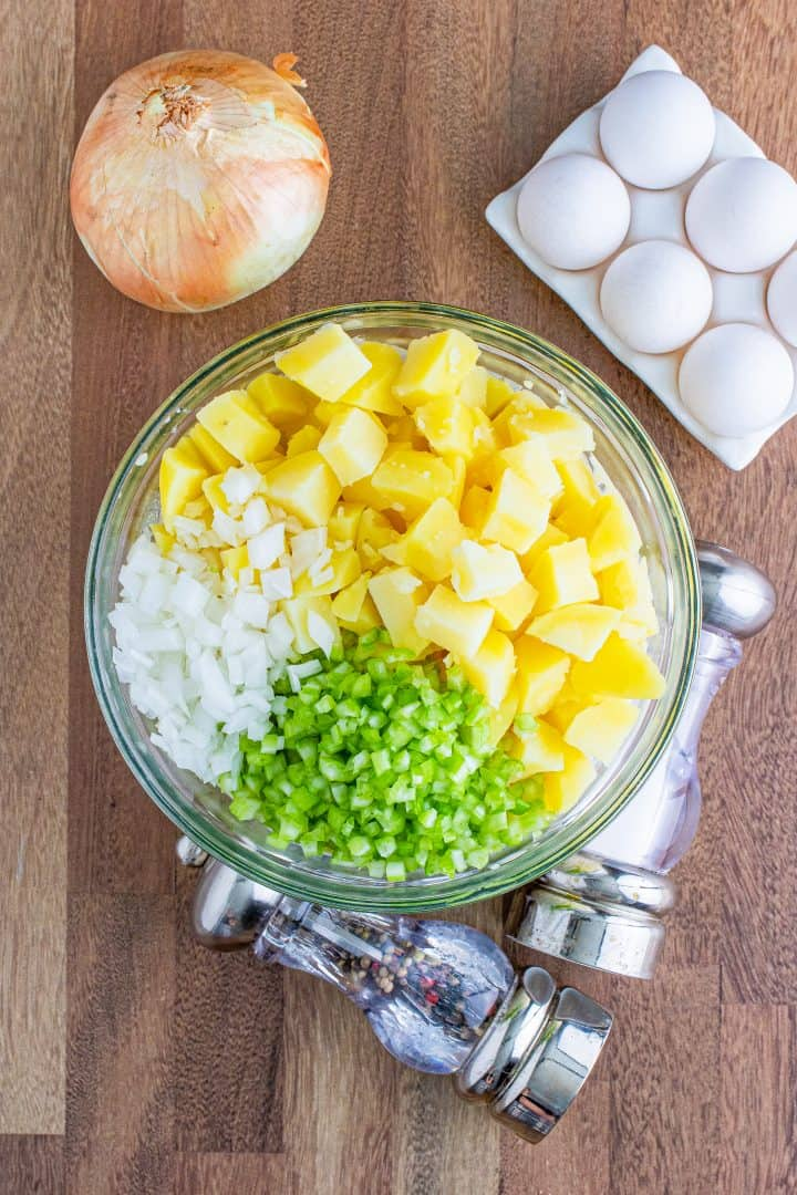 cooked diced potatoes, diced celery and diced onion added to dressing mixture in clear bowl