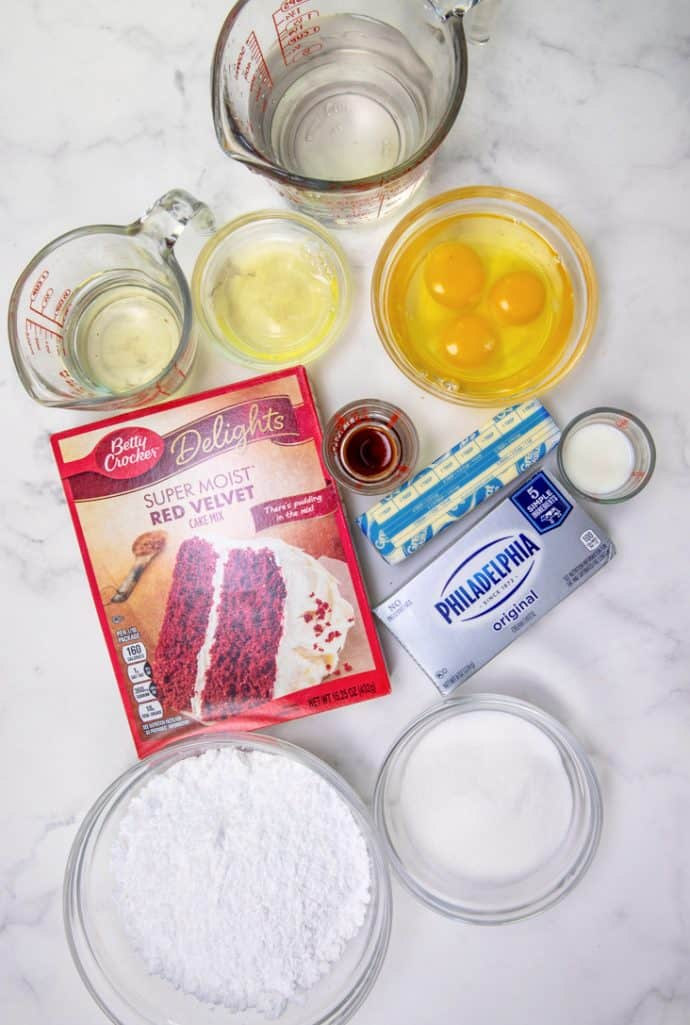 Red Velvet Cheesecake Cake ingredients: red velvet cake mix, eggs, oil, water, cream cheese, butter, powdered sugar, vanilla extract, milk