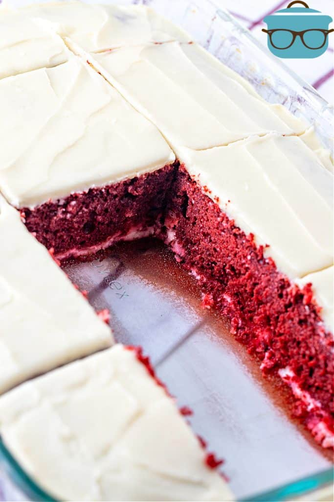 finished red velvet cake shown sliced inside clear baking dish with two slices removed