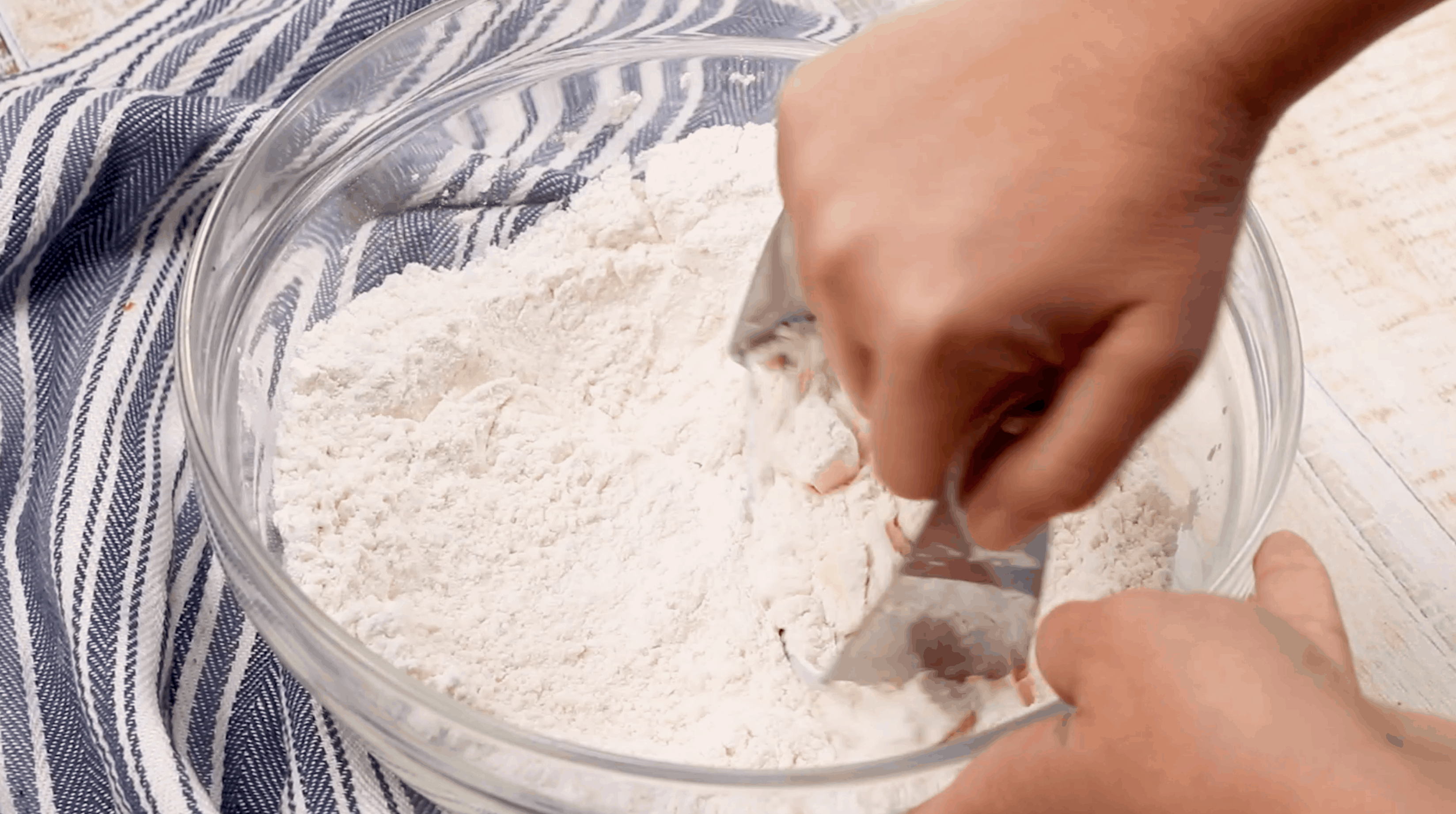 PASTRY CUTTER IN A BOWL OF FLOUR PUSHING DOWN THE CUBES OF BUTTER
