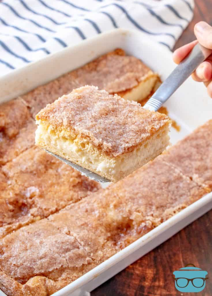 slice of sopapilla cheesecake bar being scooped out of a baking dish