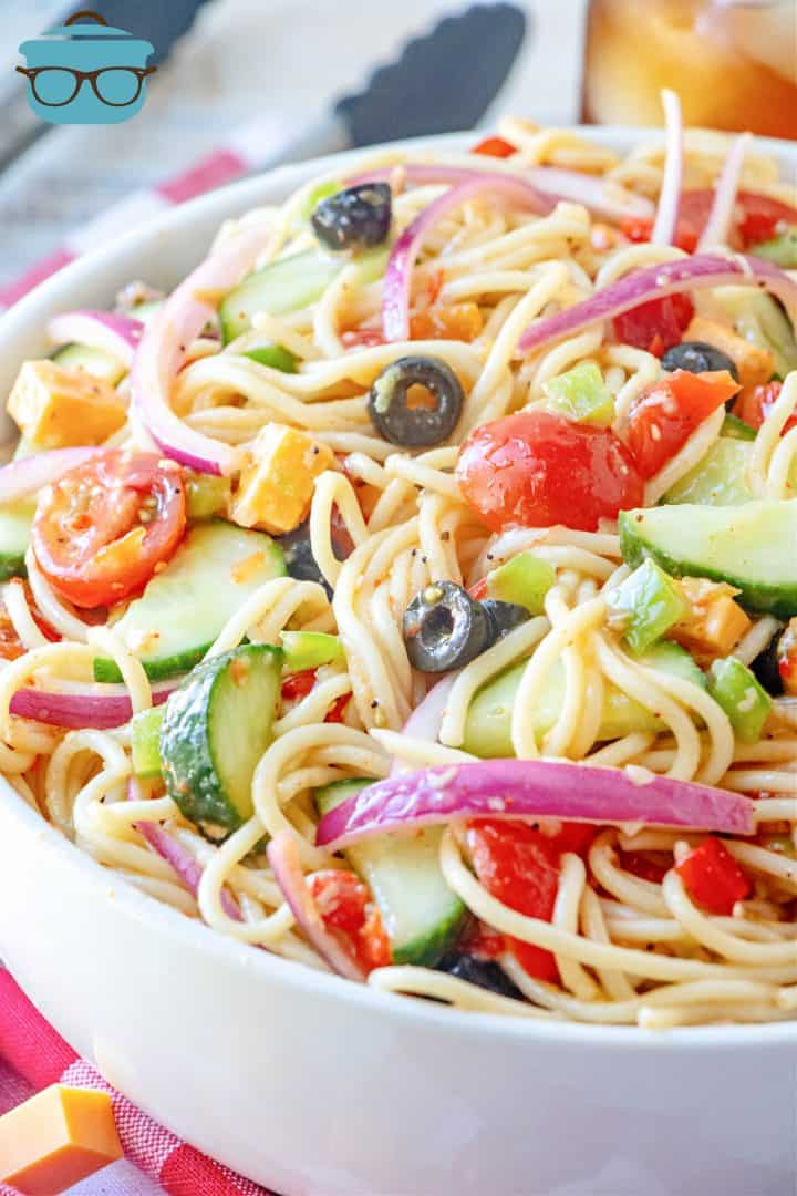 close up photo of spaghetti salad in a large white bowl