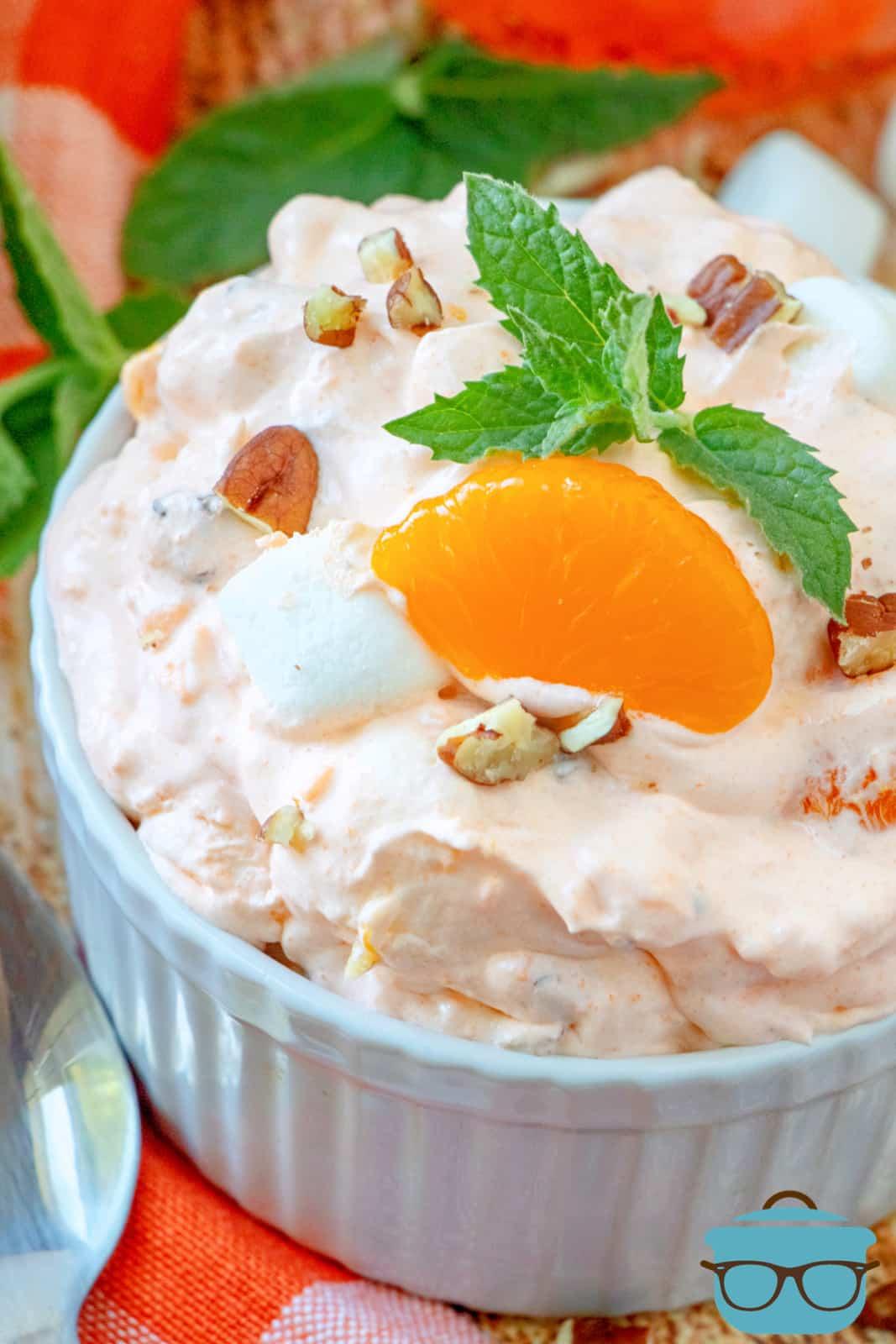 closeup photo of orange fluff dessert in white ramekin, topped with a mandarin orange slice and a sprig of mint.