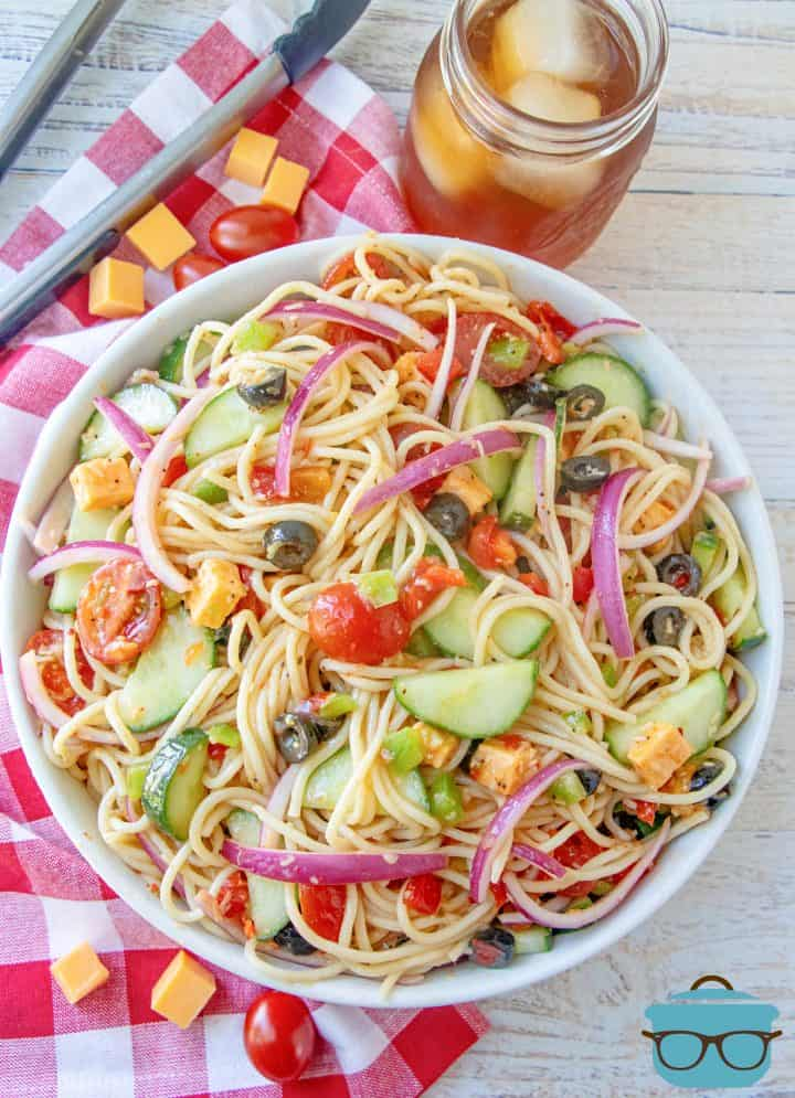 overhead shot salad made with spaghetti and vegetables in a large white bowl
