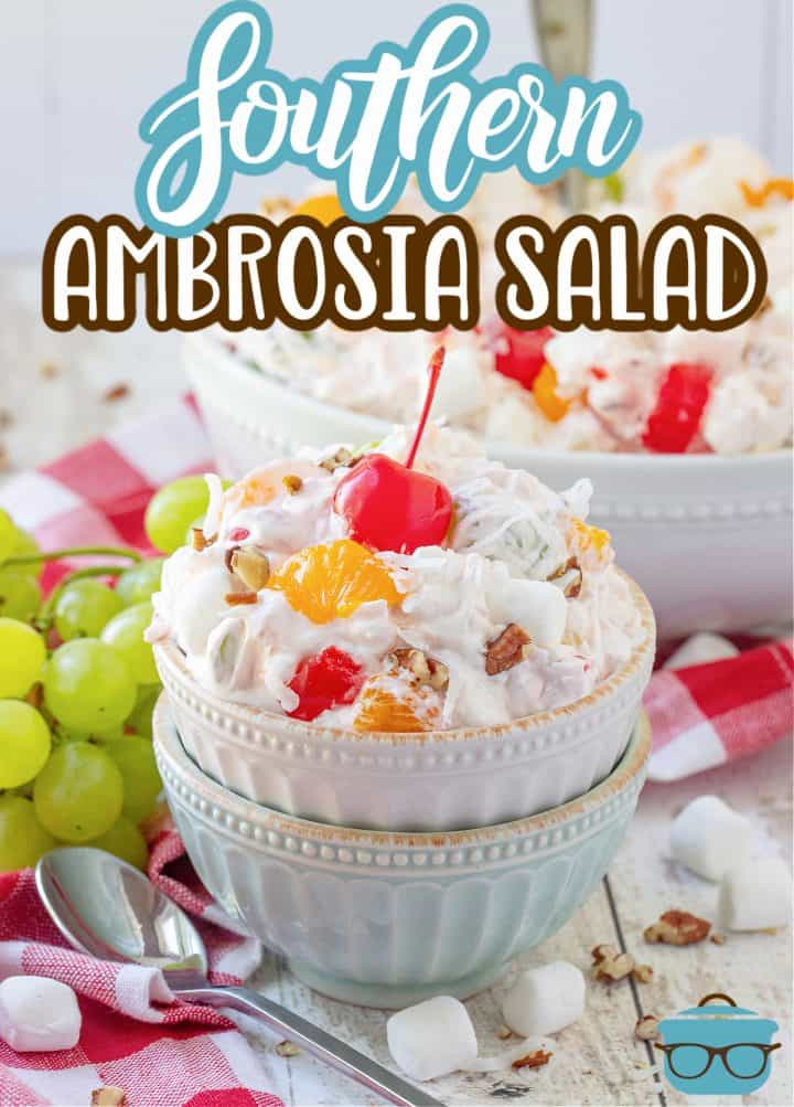 Southern Ambrosia Salad recipe from The Country Cook, a white and blue bowl stacked on top of each other, a serving of ambrosia salad shown in top bowl with a maraschino cherry on top and a bunch of green grapes in the background.