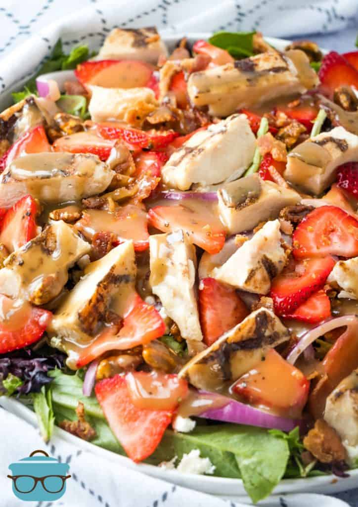 Strawberry Fields Salad shown topped with balsamic dressing and in a white salad bowl