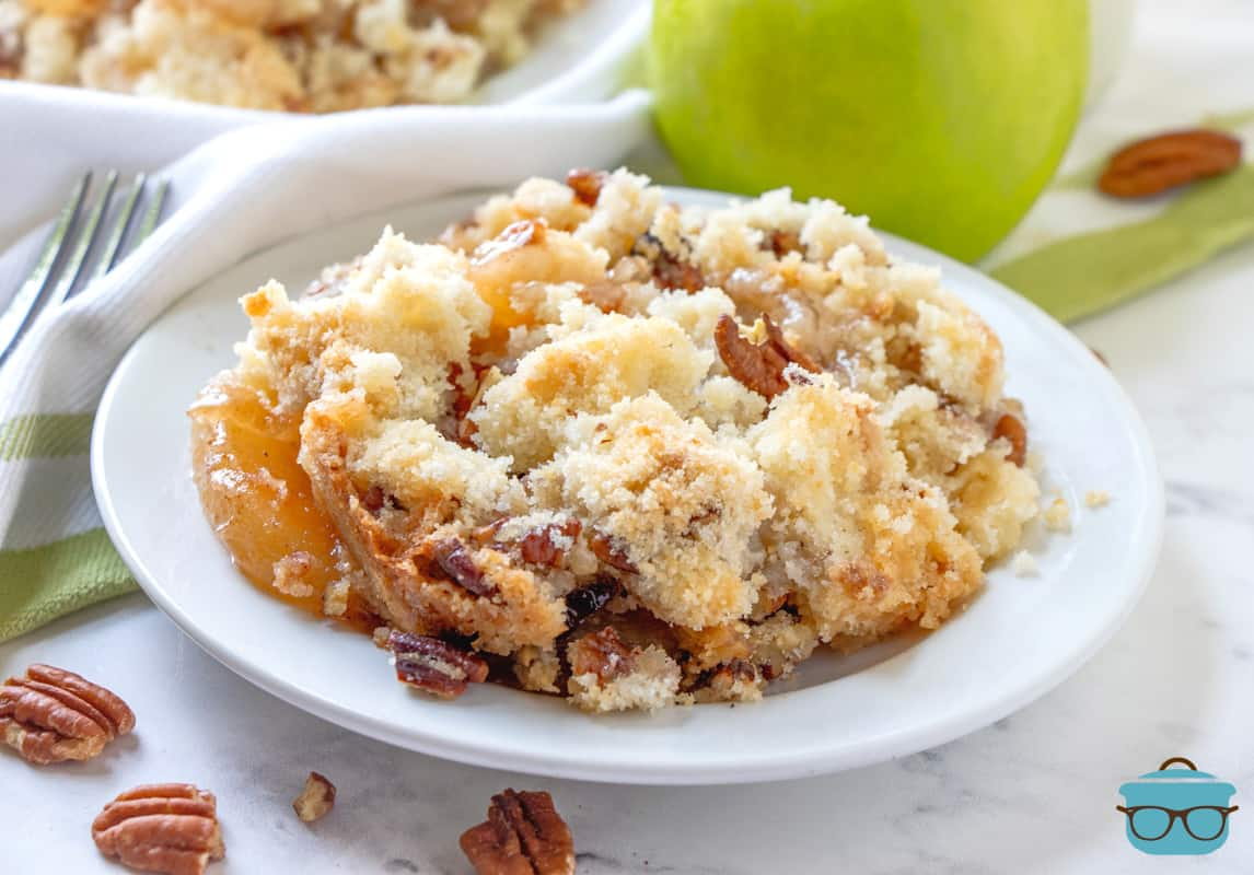 a serving of apple crisp on a white plate with a green apple in the background and pecans in the foreground