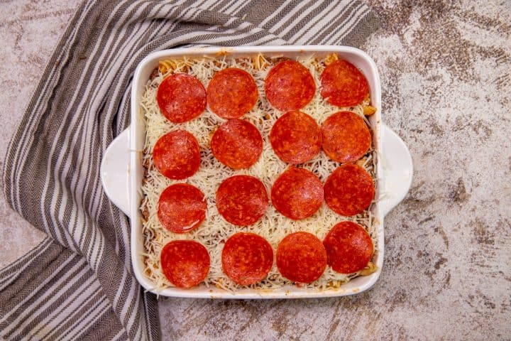 pepperoni slices placed in even layers on top of shredded mozzarella in dish.