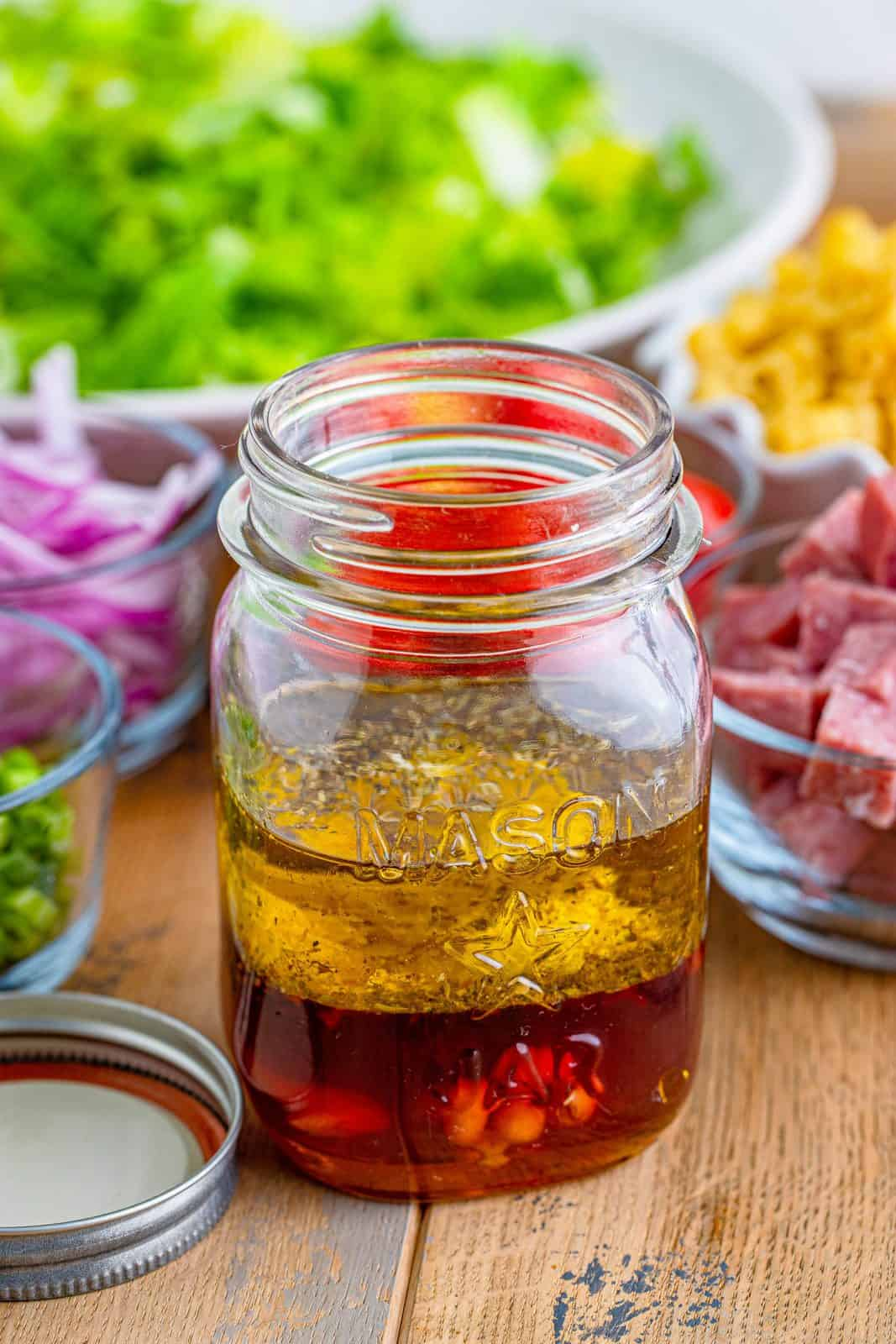 Italian chopped salad ingredients added to a mason jar.