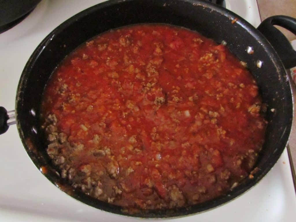 spaghetti sauce and water added to cooked ground beef in a large pan