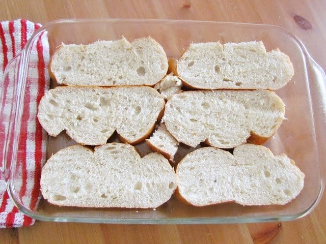 sliced French bread in the bottom of a 9x13 casserole dish