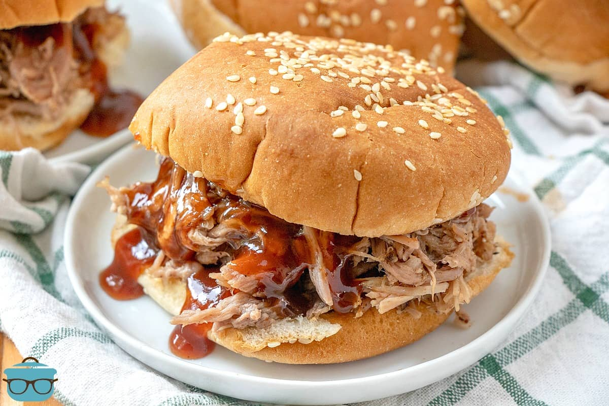 SLOW COOKER PULLED PORK ON A BUN WITH A DRIZZLE OF BBQ.