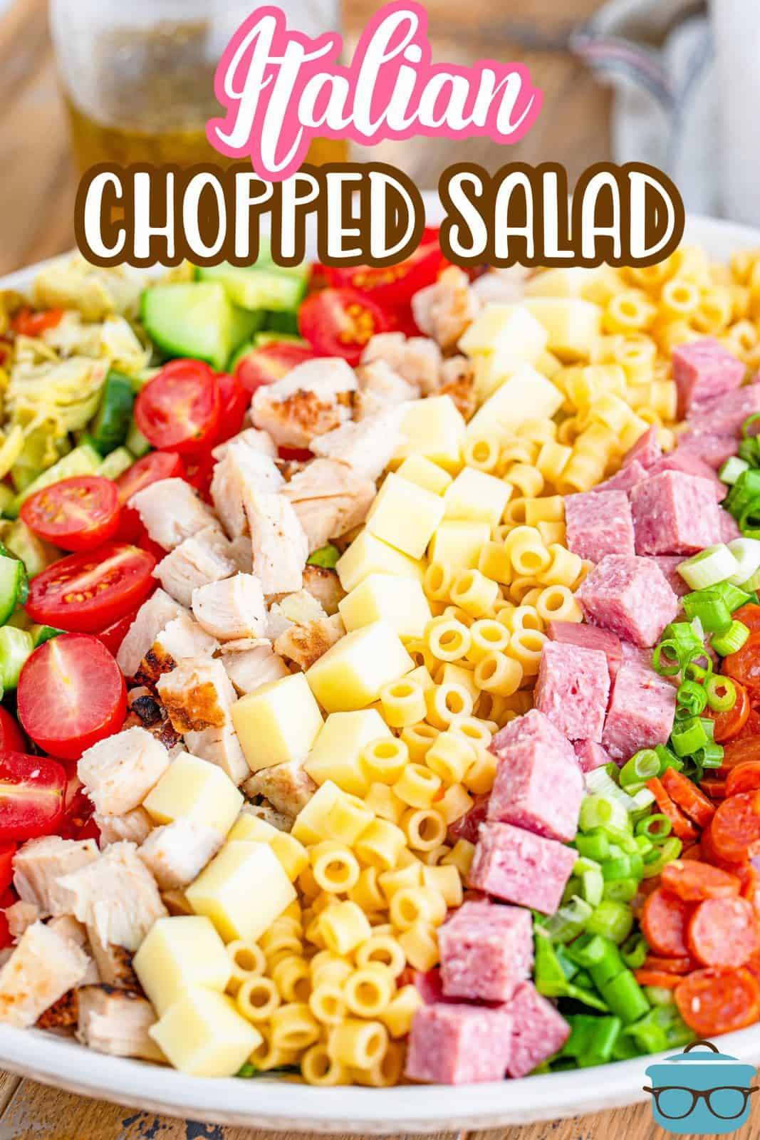 Italian Chopped Salad recipe with homemade dressing recipe from The Country Cook. Rows of each ingredient lined up in a large white bowl
