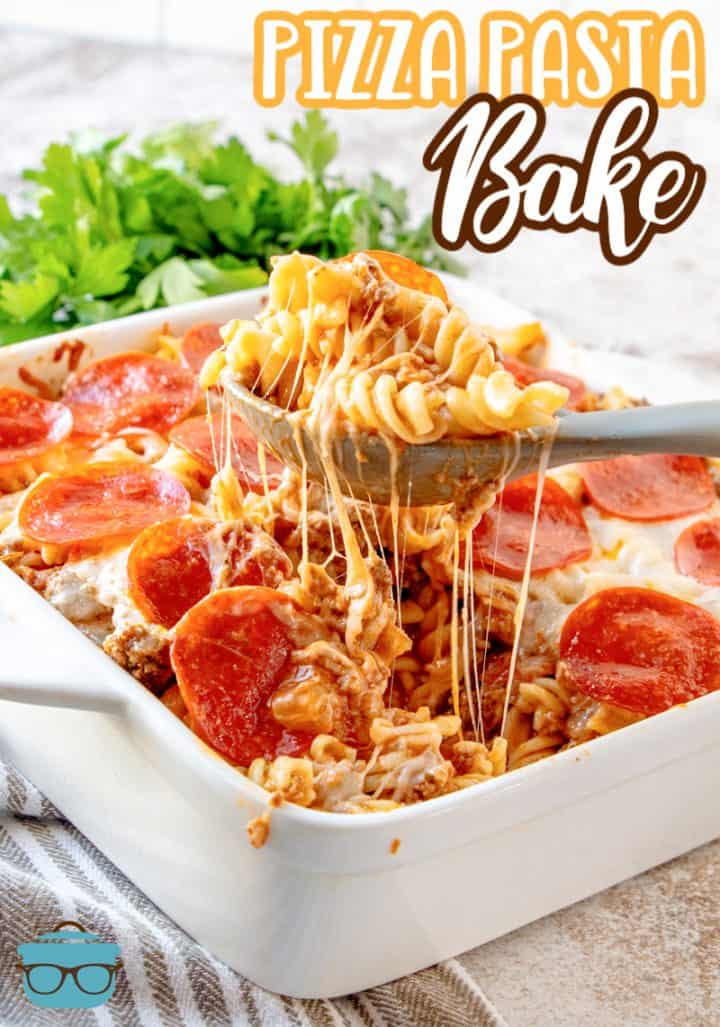 Pizza pasta fully cooked in a white casserole dish with a spoon lifting up a serving out of the dish.