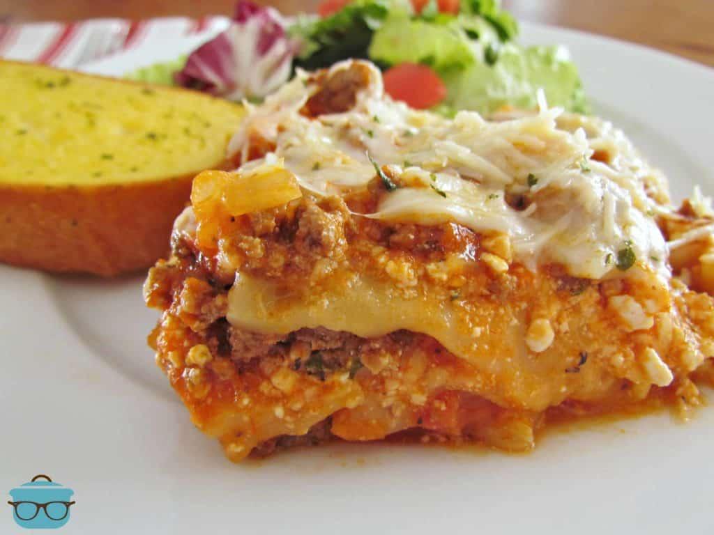 Crock Pot Lasagna slice on a plate with garlic bread with salad