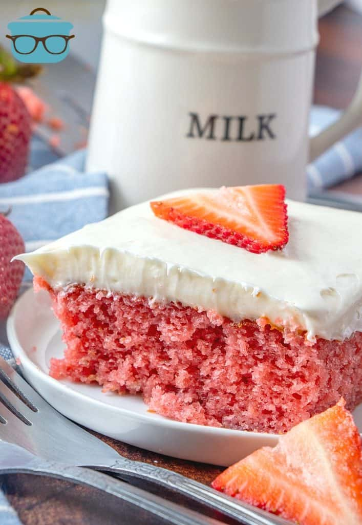 slice of strawberry cake on a plate with forks