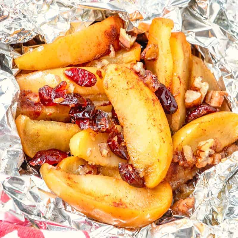 Sliced apples, cranberries, brown sugar, and pecans cooked in aluminum foil