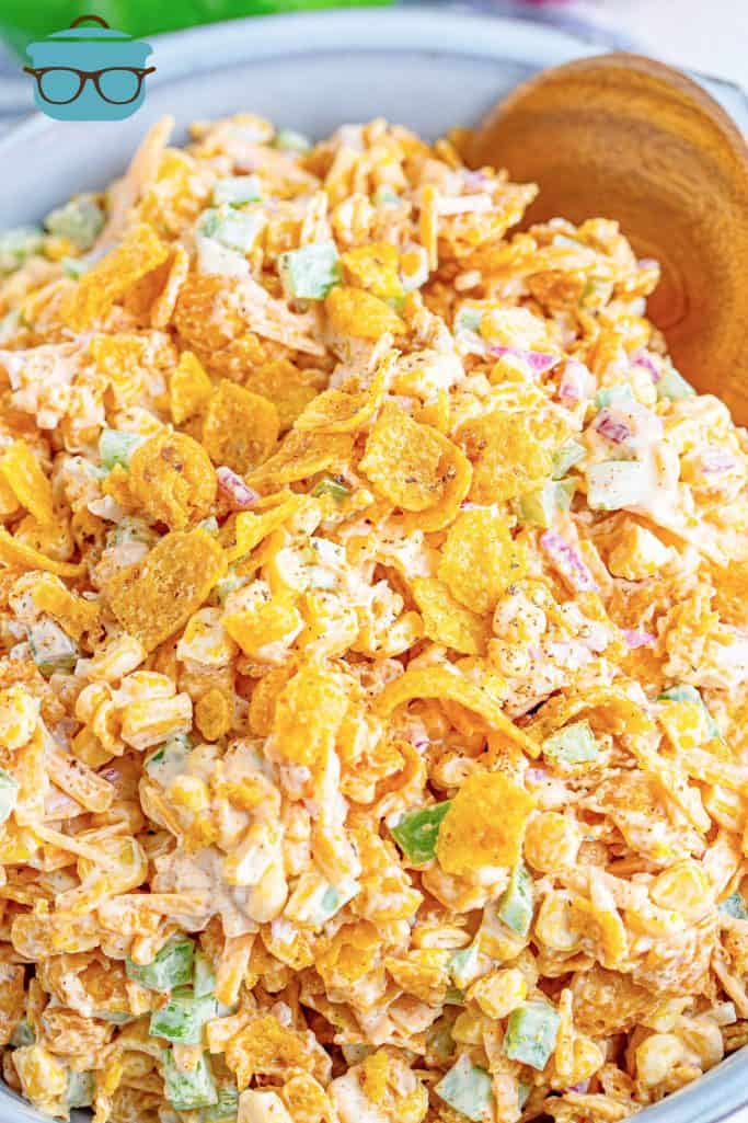 closeup photo of frito corn salad in a bowl with a wooden spoon on the side