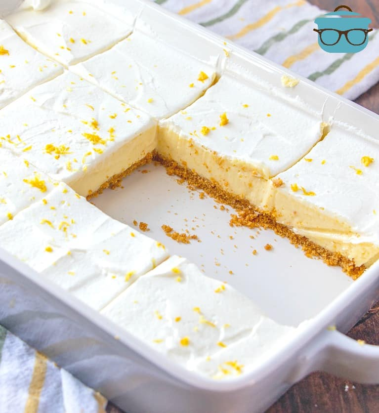 Homemade Creamy Lemon Bars, sliced, in a white baking dish, shown with two slices removed from dish