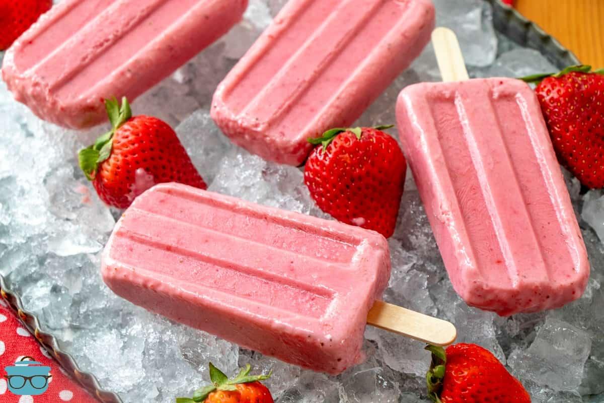 strawberry Greek Yogurt Popsicles on ice with fresh strawberries.