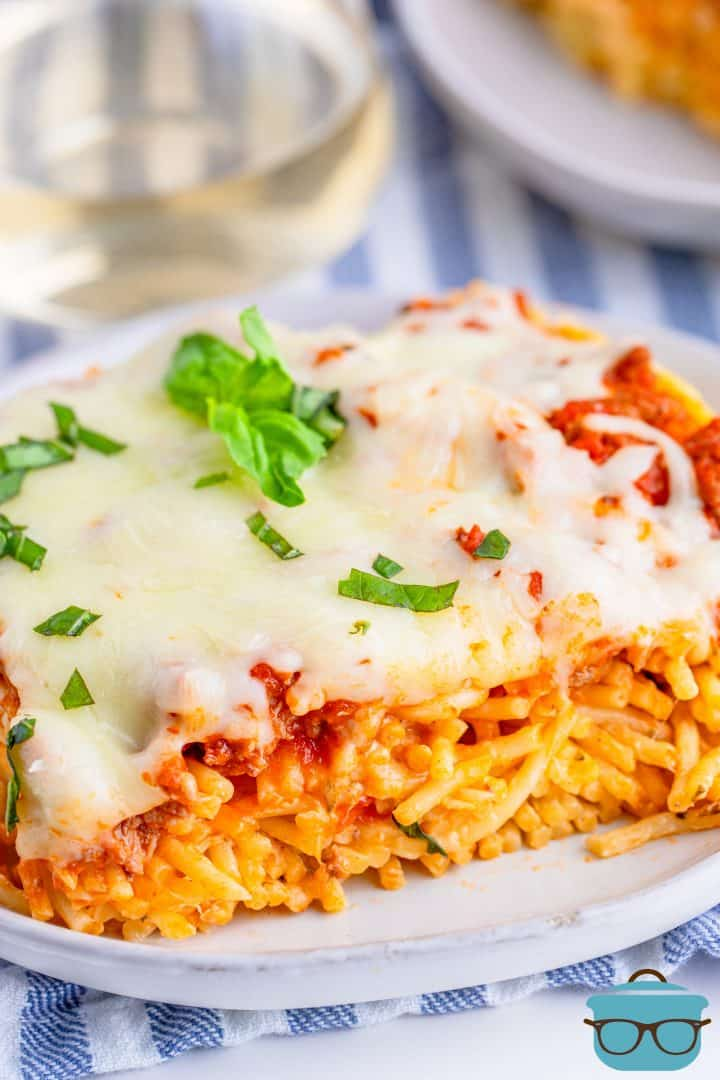 close up photo of a slice of baked spaghetti on a white plate