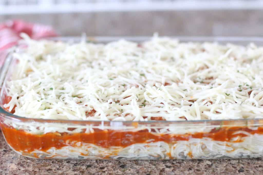 shredded mozzarella cheese on top of layers of spaghetti sauce and Alfredo noodles