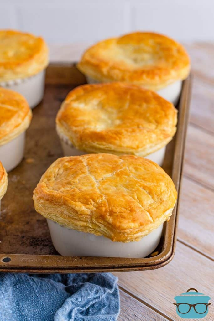 fully baked individual chicken pot pies in ramekins with golden brown puff pastry tops