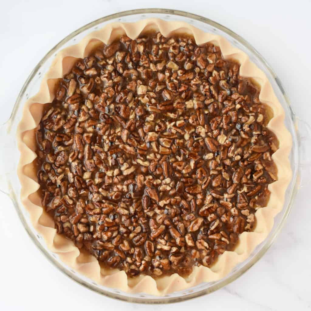 Pecan pie just before baking (showing chopped pecans floating to the top of the batter)