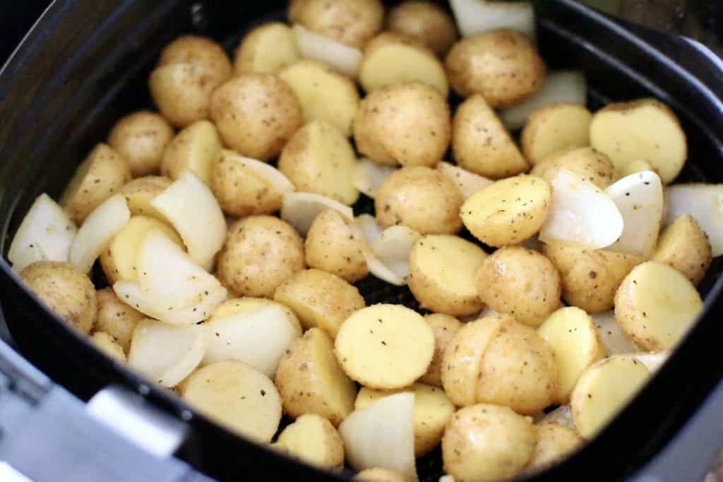 seasoned potatoes and onions in the basket of a 6-quart air fryer