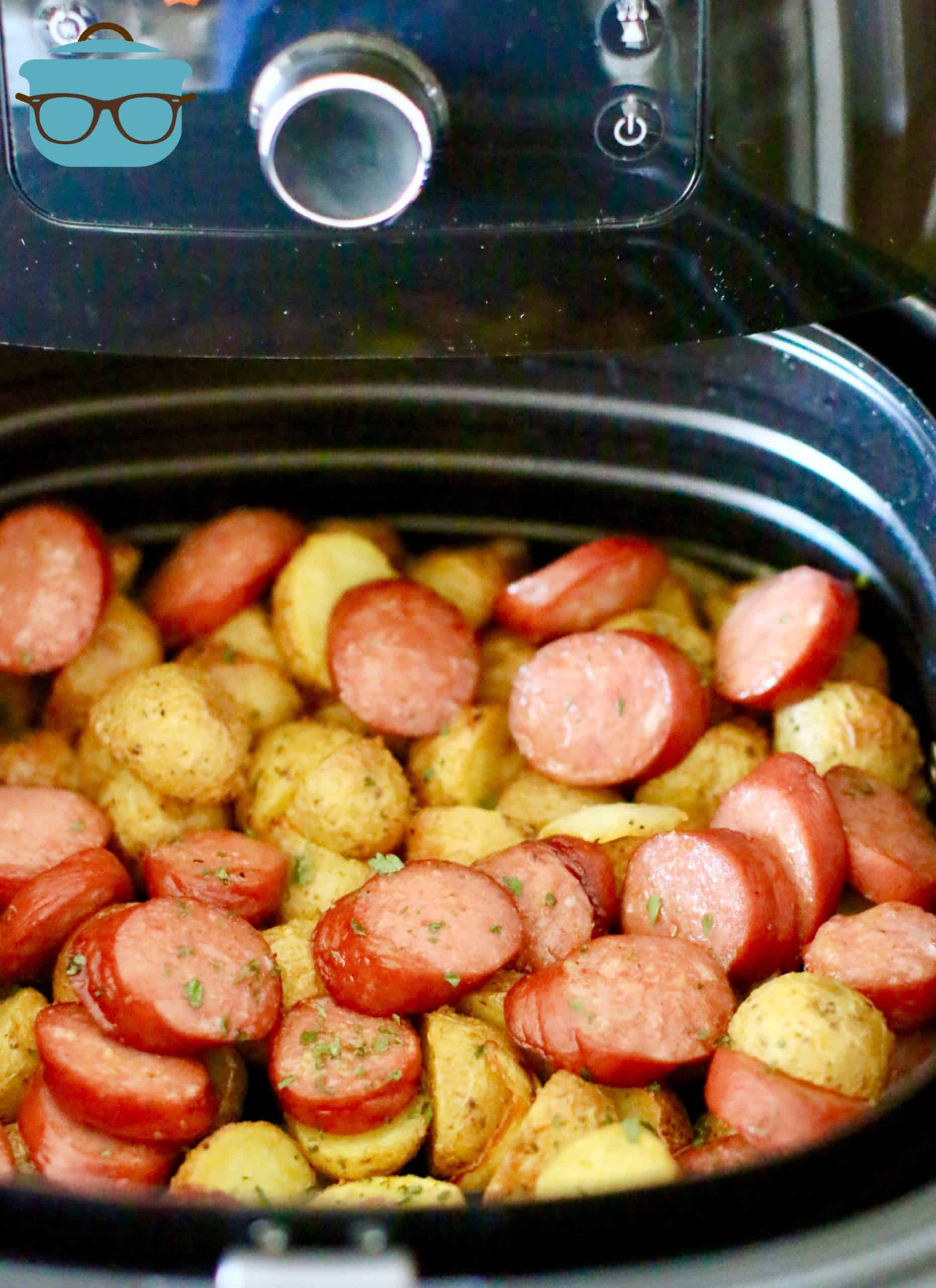 finished, air fried potatoes, onions and smoked sausage shown in the air fryer basket.