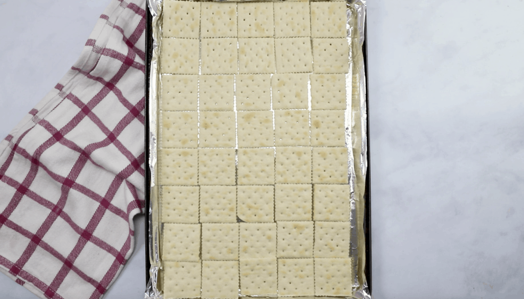 saltine crackers in a single layer on a cookie sheet