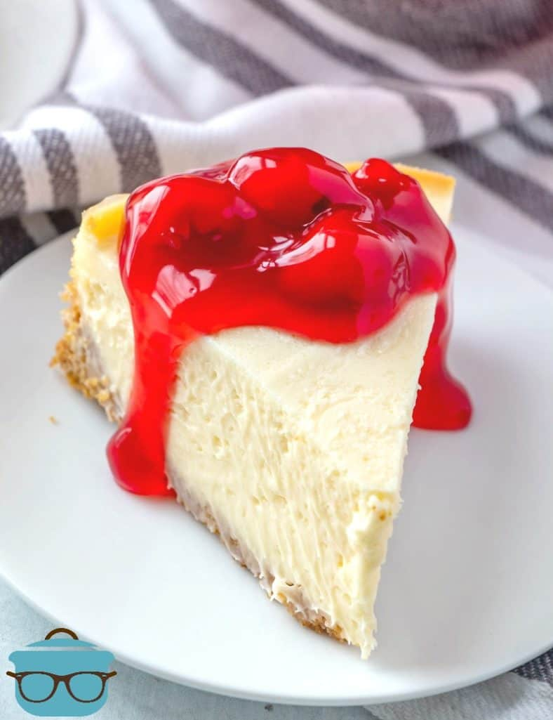Instant Pot Cheesecake, slice on a white plate topped with cherry pie filling