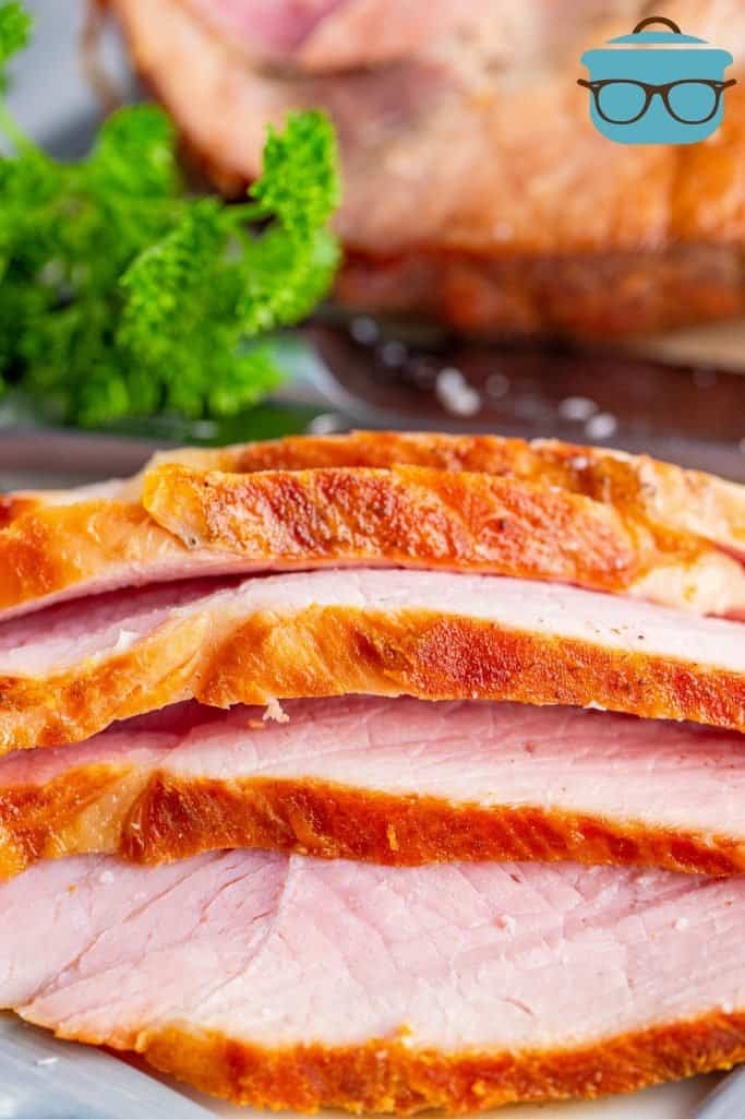 close up photo of four thinly sliced pieces of cooked ham on a white plate with fresh parsley in the background