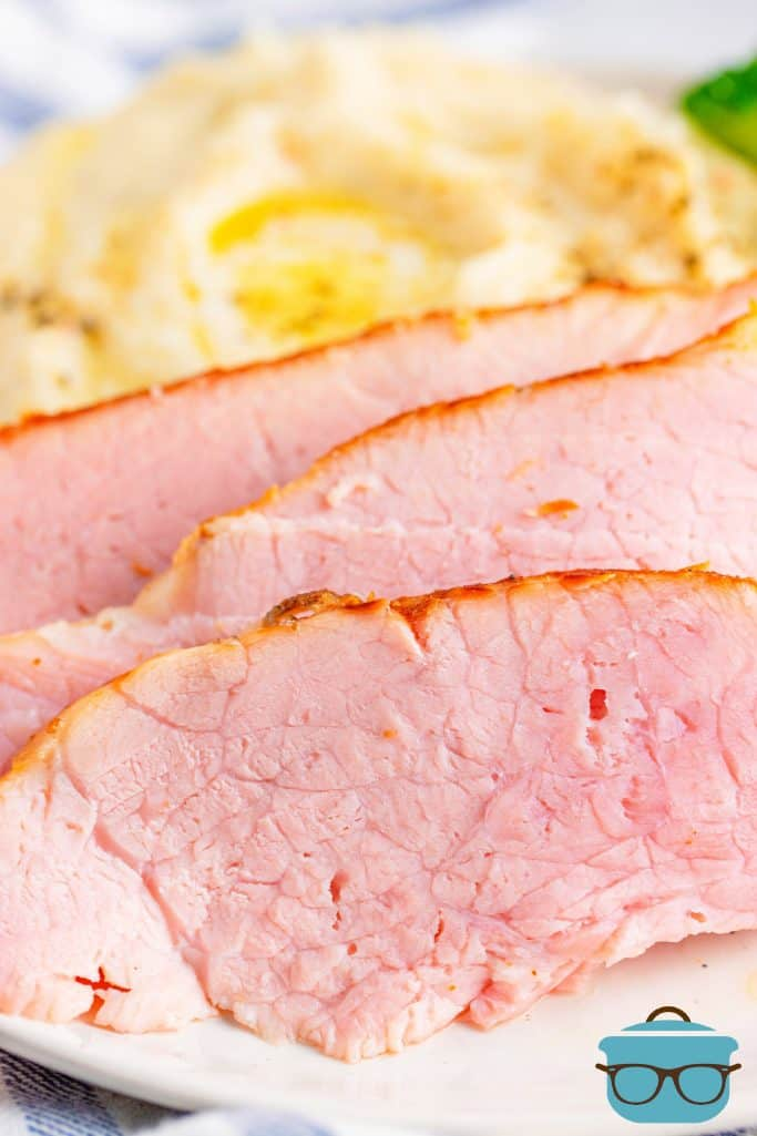 Instant Pot Ham, slices shown on a plate with mashed potatoes