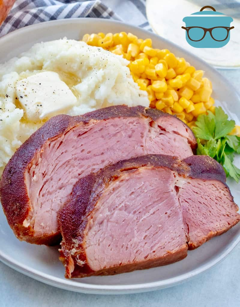 Sliced Ham on a plate with mashed potatoes and corn on a plate