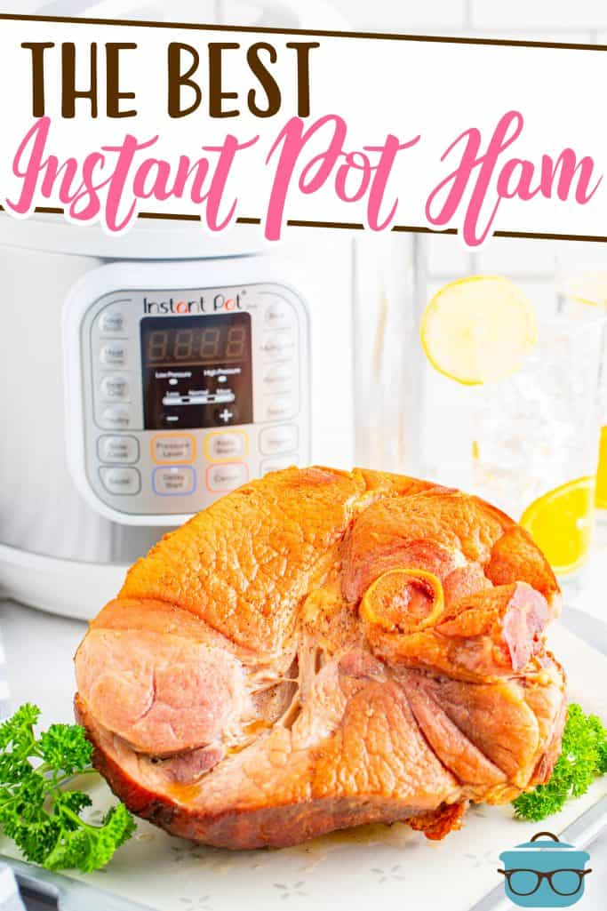 The Best Instant Pot Ham, whole ham shown on a white platter with green parsley around it and a white Intstant Pot appliance in the background