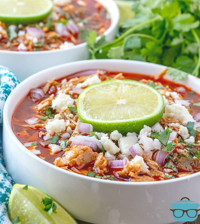 finished, Instant Pot Pork Chili topped with Cotija cheese, diced onions and a lime