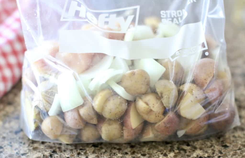 large zip top plastic bag full of potatoes, chicken and onions and seasonings mixed together