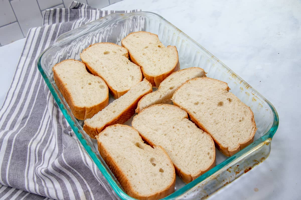 sliced French bread in the bottom of a 9x13 inch casserole dish.